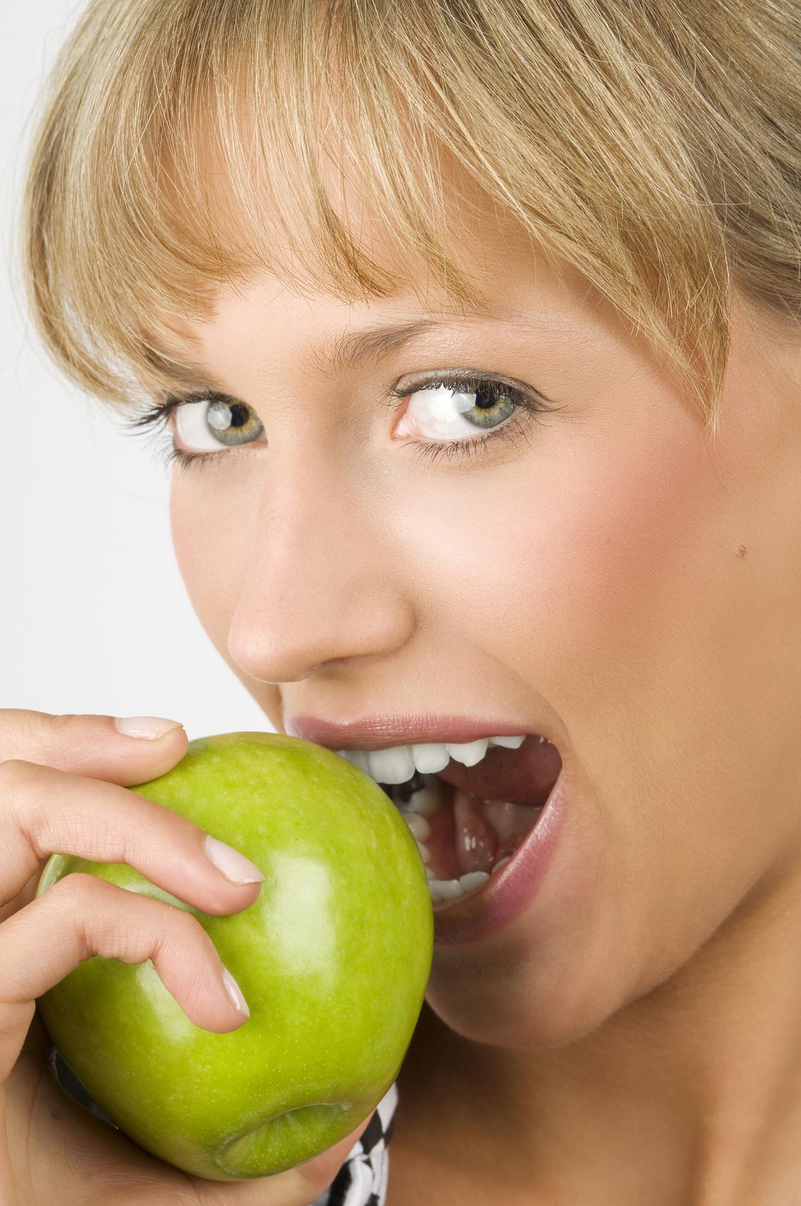 Frau beißt in Apfel